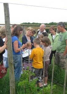 Een groep met diverse leeftijden krijgt uitleg in de biologische tuin van Sprankenhof met speurtocht voor de kinderen