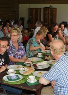 Groep mensen geniet aan tafel van theeleut hightea met diverse huisgemaakte zoete en hartige lekkernijen bij Sprankenhof Udenhout Tilburg