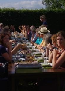 Groep mensen geniet buiten in de boomgaard aan tafel van theeleut hightea met diverse huisgemaakte zoete en hartige lekkernijen in Udenhout