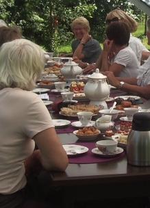 Groep mensen geniet buiten in de boomgaard aan tafel van theeleut hightea met diverse huisgemaakte zoete en hartige lekkernijen