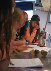 leerlingen middelbare school werken in groepjes aan diverse opdrachten aan lesbrief gezonde voeding