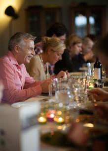 Groep mensen vergaderen bij etenstijd in bijzondere vergaderlocatie Udenhout