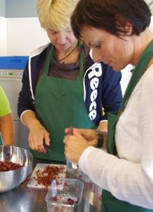 Twee dames maken fruit schoot tijdens biologische workshop fruitbereiding in kookstudio Sprankenhof in Udenhout