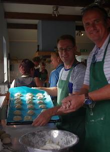 Twee heren leggen deegbolletjes op bakplaat tijdens workshop boerentheeleut in kookstudio Udenhout