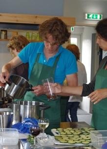 jongeman staat met pan in de hand in kookstudio Sprankenhof bij een biologische workshop lunch